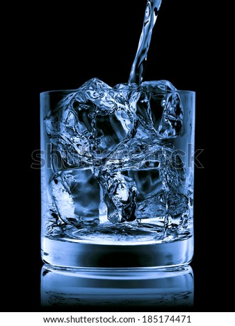 Pouring Scotch Whisky in Glass with perfect ice isolated on black - stock photo