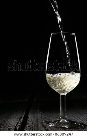 pouring sherry white wine in an traditional sherry cup - stock photo