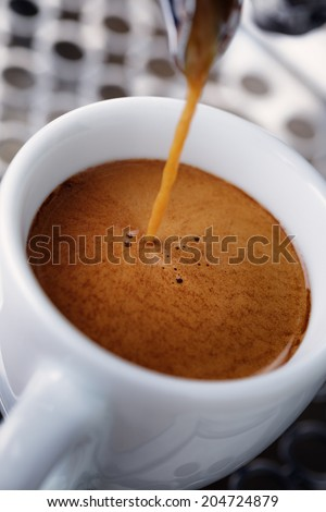 pouring simple espresso with coffee machine, close up - stock photo