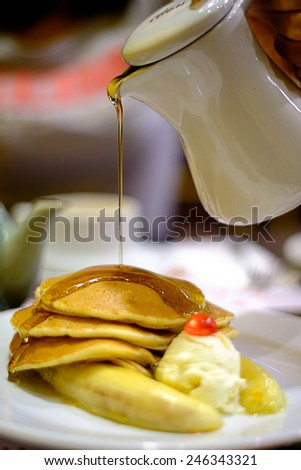 Pouring syrup on pancakes, banana.