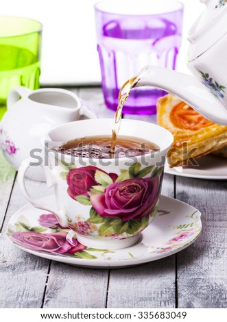 Pouring tea into cup of tea on white background - stock photo