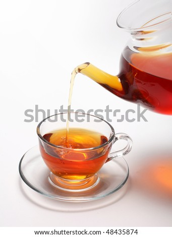 Pouring tea to a teacup - stock photo