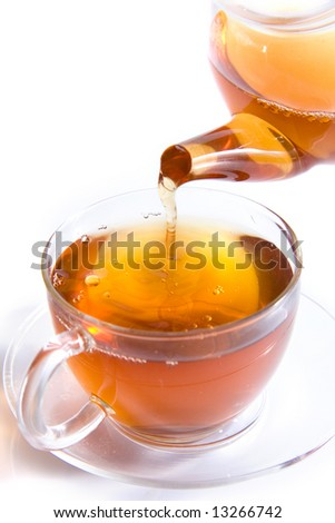 Pouring tea to a transparent teacup - stock photo