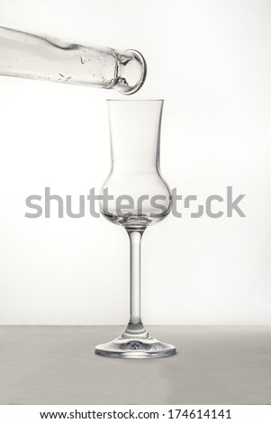 Pouring the Grappa into a glass - stock photo