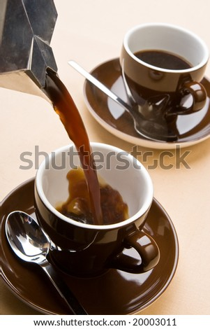 Pouring the hot coffee into a cup - stock photo
