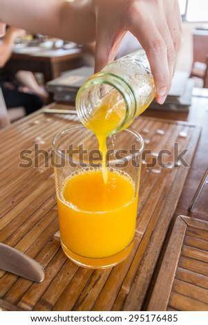 Pouring the orange juice - stock photo
