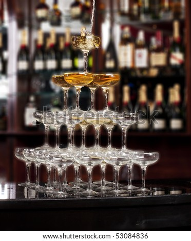 Pouring the wine along stack of glasses - stock photo