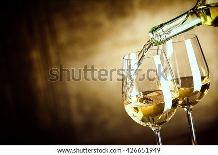 Pouring two glasses of white wine from a bottle in a close up view of the wineglasses over an abstract brown blue background with copy space - stock photo