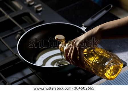 Pouring vegetable oil into frying pan - stock photo