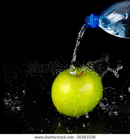 pouring water from a bottle on green apple  on black background