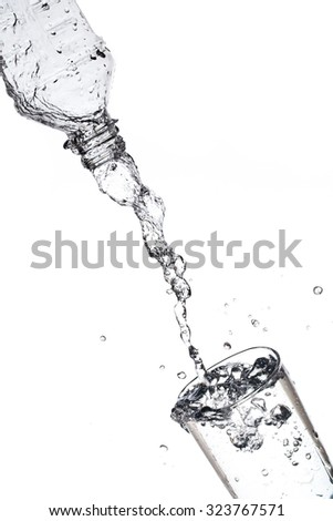 Pouring water from bottle into glass isolated on white background