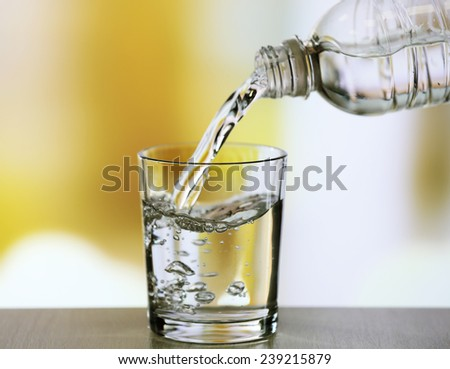 Pouring water from bottle on  glass on light background - stock photo