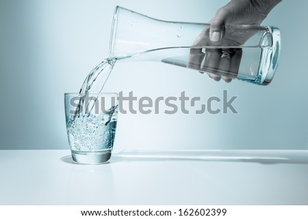Pouring water from pitcher into a glass  - stock photo