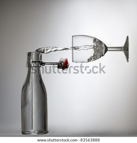 Pouring water in a glass, illusion - stock photo