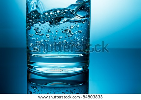 pouring water in glass bottom closeup in blue light