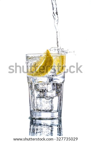 Pouring water in glass isolated on black background - stock photo