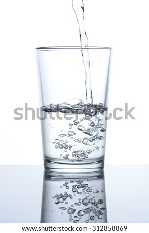 Pouring water into a glass on white background - stock photo