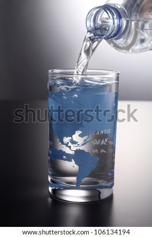 pouring water into a glass printed world map