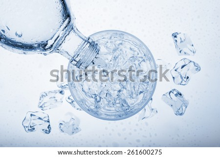 pouring water into glass with ice cube from a bottle, on blue background - stock photo