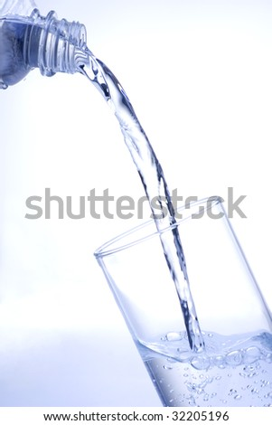 Pouring water into glass with shaded background - stock photo
