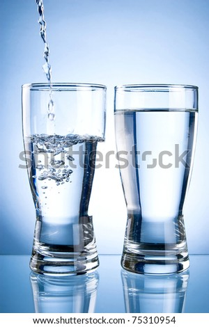 Pouring water into glasson and Glass of water on a blue background - stock photo