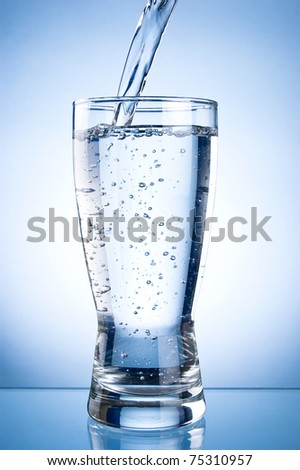 Pouring water into glasson on a blue background - stock photo