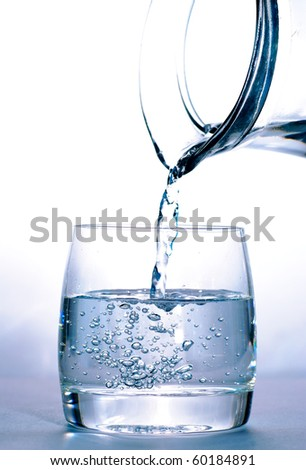 Pouring water into the glass from jug - stock photo