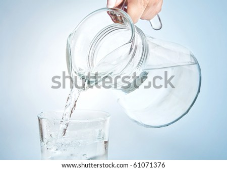Pouring water into the glass from jug