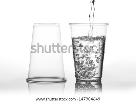 Pouring water into transparent expendable mug made of plastic and second mug standing empty upside down, white background with reflections, horizontal orientation, objects in studio shot, nobody. - stock photo