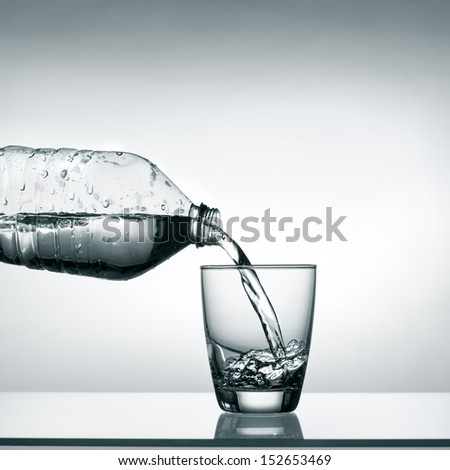 Pouring water into transparent glass - stock photo