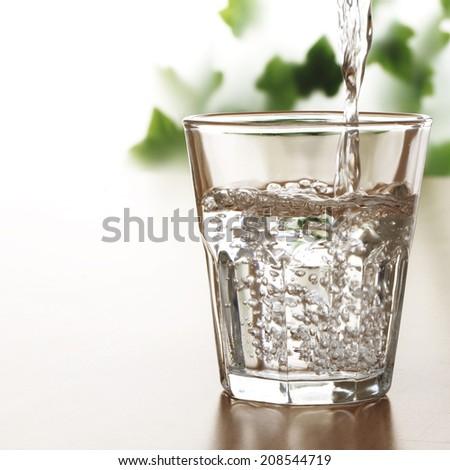 pouring water on a glass on the table - stock photo