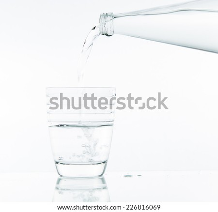 Pouring water on glass on over white background
