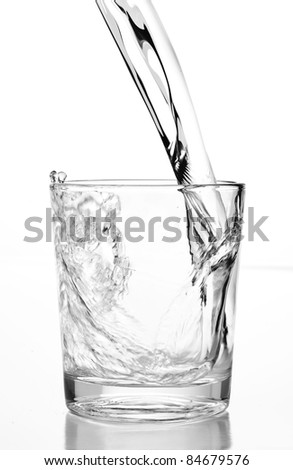 pouring water on glass on white background - stock photo