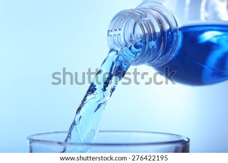 Pouring water on light background - stock photo