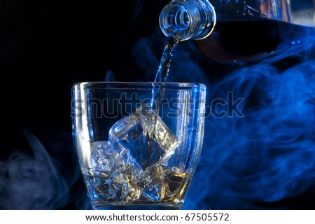 Pouring Whisky . Brandy with ice - stock photo
