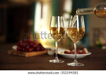 Pouring white wine from bottle into the wineglass on the table over blurred background - stock photo