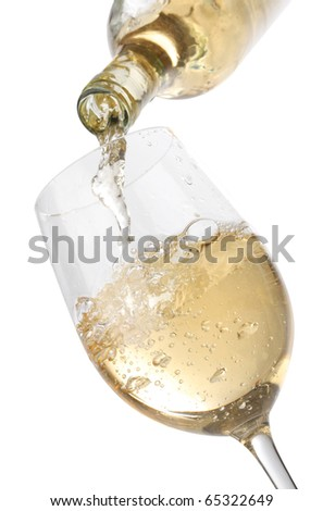Pouring white wine into a glass, isolated on white background - stock photo