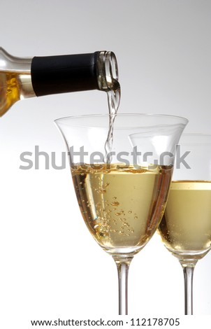 Pouring white wine into wine goblets - stock photo