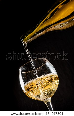 pouring white wine into wineglass