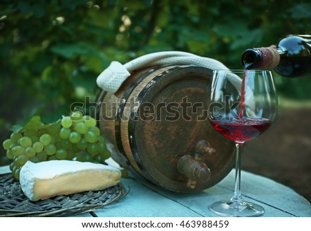 Pouring wine in glass in vineyard