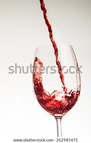 Pouring wine in glass on background