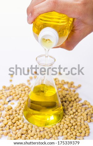 pouring yellow soya bean oil into test tube glass - stock photo