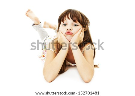 Pouting little girl lying on floor. Isolated on white background  - stock photo