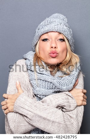 pouting sophisticated beautiful young blond woman feeling warm and sexy wearing grey winter hat and scarf for valentines day, studio shot