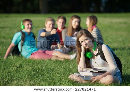 Pouting teen girl near group on grass outdoors - stock photo