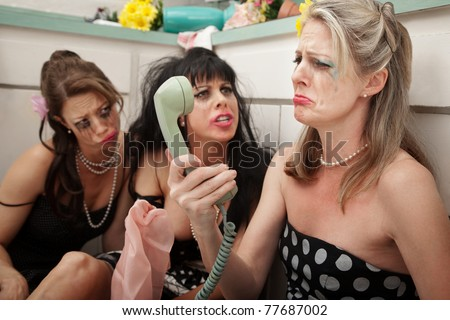 Pouting woman on phone with friends in kitchen - stock photo