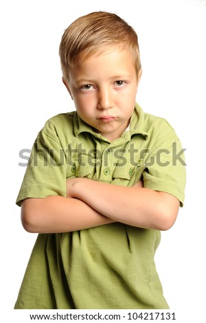 Pouting Young Boy. Seven year-old boy standing with his arms crossed and expressing negative emotions. Isolated on white. - stock photo