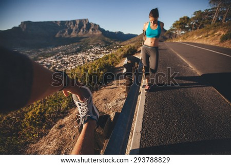 POV shot of man stretching his leg with woman exercising by a road guardrail. Young people relaxing their muscles after morning run outdoors on country road. - stock photo