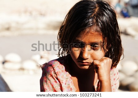 poverty, portrait of a poor little Indian girl lost in deep thoughts - stock photo