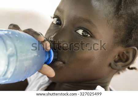 Poverty Symbol: African Black Girl Drinking Heathy Fresh Water. Poverty Symbol in Mali: African Black Girl Drinking Heathy Fresh Water from a bottle. - stock photo